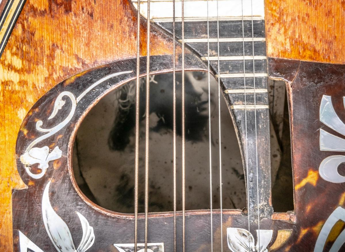 Mandolin. Något nött och trasig. I botten av mandolinen finns en bild av förutvarande ägaren La Bella Ingeborg, cirkusartist från gävle. Till mandolinen finns ett brunt fodral av brunt bomullstyg. Skänkt till museet av ägarinnans släktingar, familjen Bazola - Bergman genom Maria Bergman maj -01. Se bilaga.