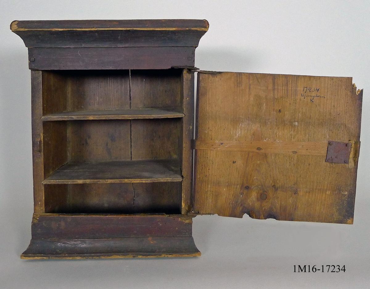 Väggskåp, häng i furu. Stomme sinkad ihop. Upptill, rakt profilerat krön, fastsatt med träplugg - nedtill liknande. Massiv dörr med gradregel på insidan. Utsidan slät förutom en utanpåliggande dekoration - romb, fastsatt med träplugg. Gångjärn och infälld låskista i järn. Nyckel saknas. Invändigt två i spår, löst liggande hyllplan. Bakstycke: en hel furubit, nu sprucken, fastsatt med spik och träplugg. Skåpet är målat i röd/brunt.