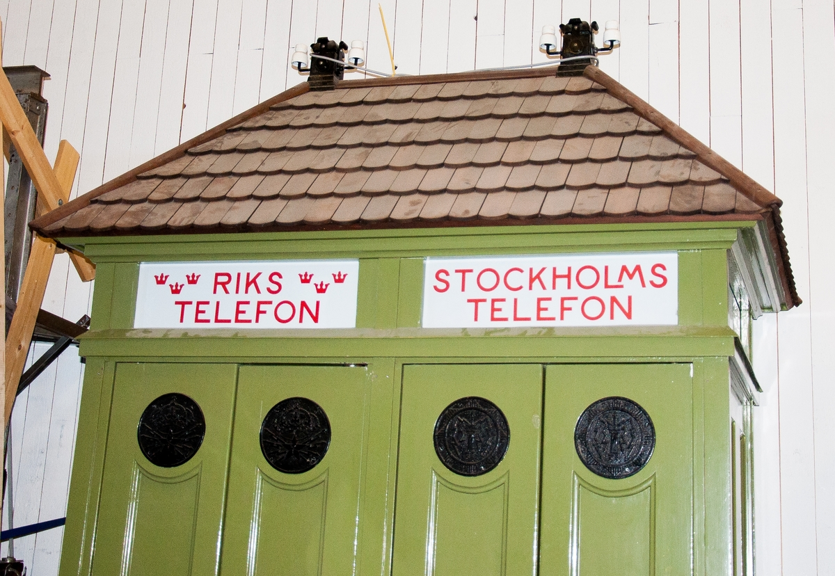 """Telefonkiosk med två talhytter, s k dubbelpagod. järnstomme med nät nedtill, insatser av trä med glasfönster, delade dörrar med dörrstängare (fjäder), spåntak samt inledningsrör med isolatorer för anslutning av blankledning. Skyltar av opalglas med texten """"Rikstelefon"""" respektive """"Stockholmstelefon"""".  Föremålsbilderna visar även interiörer med myntautomater. En äldre i trä av typ CF595 är placerad i ena hytten och en något nyare apparat i metall, en grön 10-öresapparat av typen CF596, i den andra."""