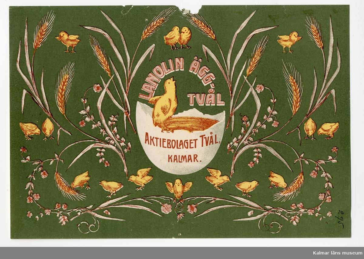 KLM 21360:3:2 Etikett, av papper, tryck av litografisk etikett. På etiketten bild av kyckling på ett äggskal, däromkring kycklingar, sädesstrå och blommor i vitt, gult, brunrött mot grön bakgrund. Etikett till tvålförpackning för beställaren Aktiebolaget Tvål, Kalmar. Varan benämnd Lanolin Ägg-Tvål. Tryckt på Janssons Litografisk tryckeri i Kalmar med nr 295. Trycket låg löst i provbok med varuetiketter mm, KLM 21360:1.