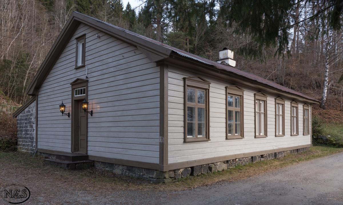 Administrasjonsbygg. Rektangulært bygg med liggende kledning og saltak. Vindu/ glassflater på alle fire sider av bygget.