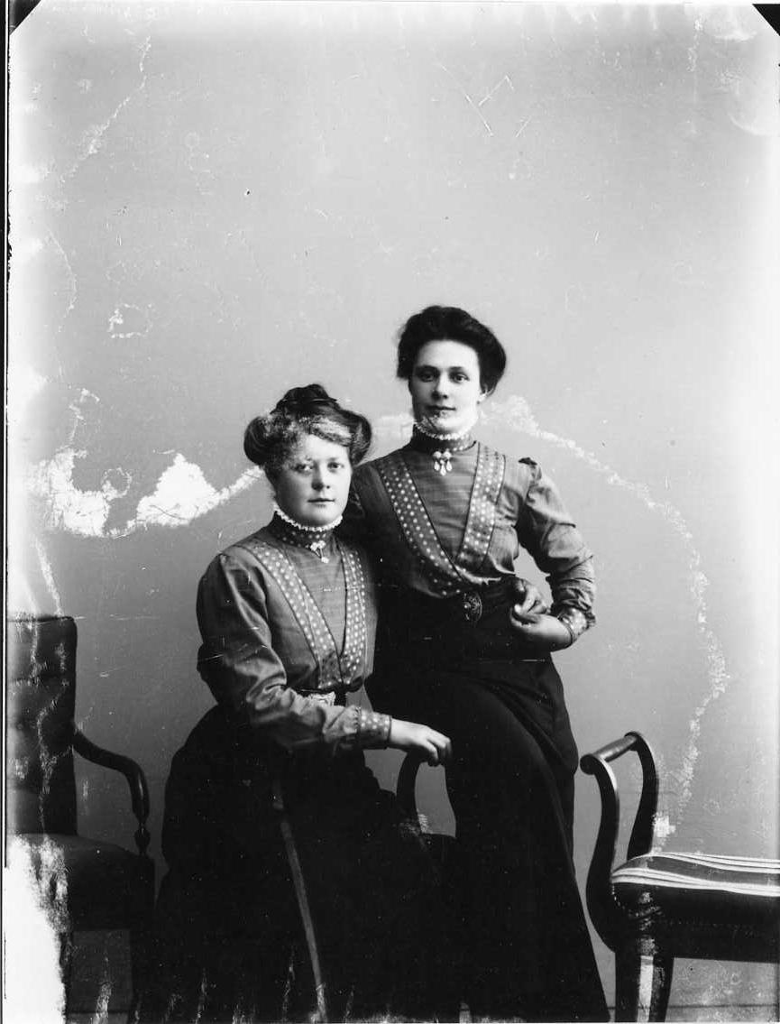 Gruppbild med två unga kvinnor som håller varandra om midjan. De är klädda på samma sätt i mörk kjol och rutig blus med prickiga band som löper över axel snett ned mot naveln. Kvinnan till vänster är Hanna Johansson från Örserum.