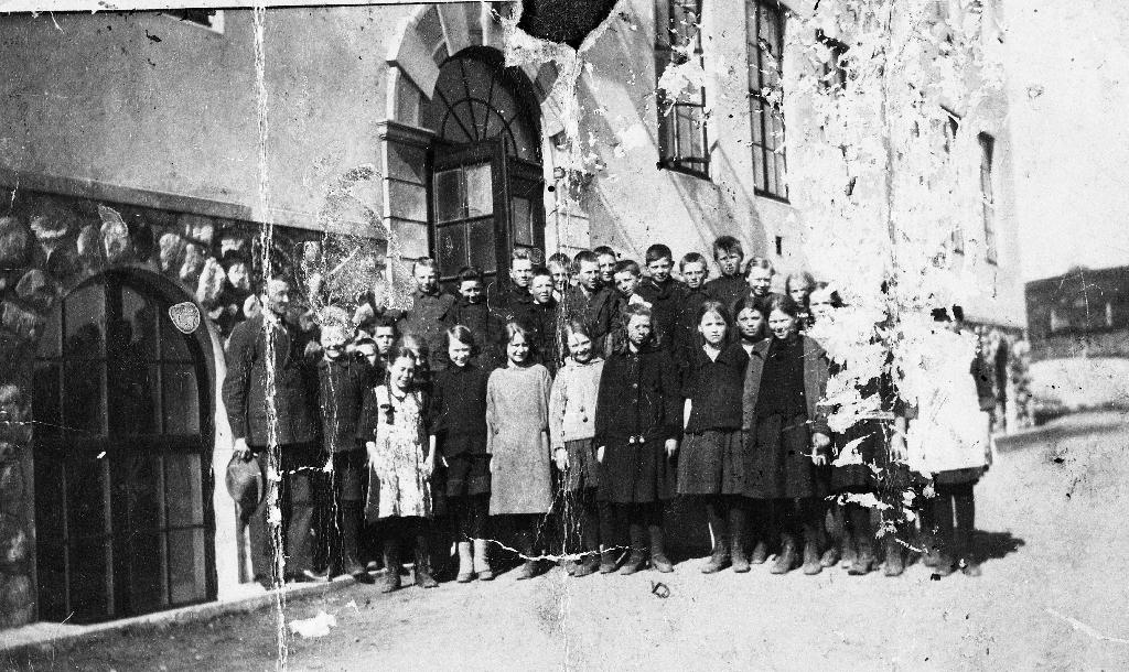 Lærar Mons Hauge og elevane i 5. klasse framfor Bryne skule i 1923. Skulen vart bygd i 1922.