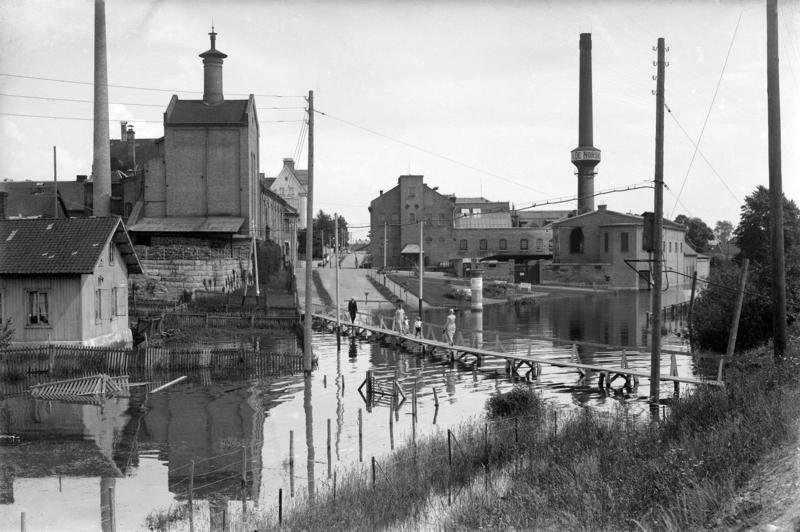 Svart-hvitt fotografi som viser en vannfylt gate med provisorisk bro over, et lite plankehus til venstre og to store murbygninger; Hamar bryggeri og melkefabrikken med en høy, rund mursteinspipe.