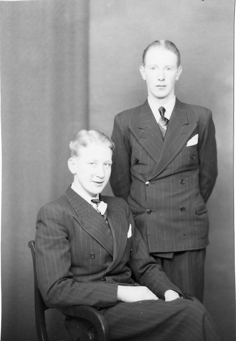 Gruppbild med två unga män, kusiner. Stående är Stig Gustavsson från Måleskog och sittande är Rune Johansson från Hövik. Bägge bär kritstrecksrandig dubbelknäppt kostym, ljus skjorta, slips och näsduk i bröstfickan.