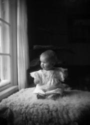 Baby på fårskinn vid fönster.