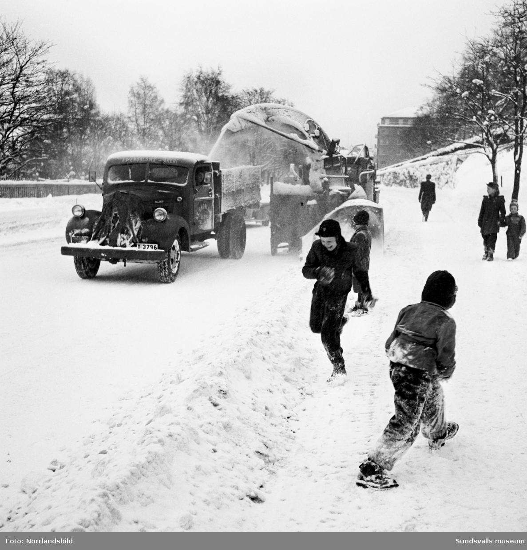Snöröjning med plog, lastbilar och snöslunga på västra Storgatan. Några barn leker en farlig lek framför snöslungan.