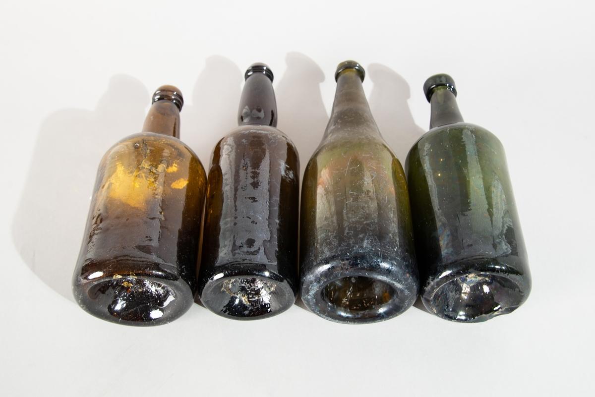 Glasflaskor, 4 st, med inåtgående botten. Två är bruna (H: 237 mm, Diam: 88 mm; och H: 275 mm, Diam 78 mm) och två gröna (H: 270 mm, Diam 95 mm; och H: 248 mm, Diam 85 mm med ett litet hål i bottnen).