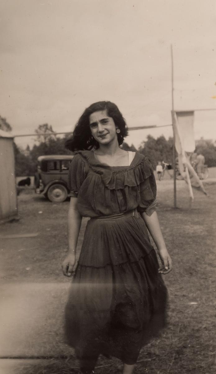 En romsk flicka står på en öppen gräsyta, i bakgrunden syns en bil och fler människor. Det är känt att romer bodde i ett läger i Sandviken under sommaren 1947. Fotografiet är taget i juni detta år.