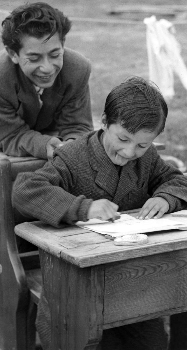 Skolundervisning för romska barn vid Frihamnen i Malmö 1954. Undervisningen skedde på uppdrag av Stiftelsen Svensk Zigenarmission. Stiftelsen Svensk Zigenarmission grundades 1945. Missionen grundades av flera religiösa samfund och bedrev ambulerande skola för svenska romer med stöd av staten. Verksamheten skedde främst under somrarna fram till slutet av 1950-talet. En lärare följde då med lägret för att undervisa både barn och vuxna i läsning, skrivning, räkning och sömnad. I en statlig utredning från mitten av 1950-talet konstaterades dock att undervisningen inte var så lyckad. Man led brist på materiella resurser. Ofta fick man ha lektion utan skolbänkar eller svart tavla. Samtidigt hade de större lägren börjat delas upp i mindre, vilket gjorde att färre elever nåddes. Lägren flyttades även femton till tjugo gånger under en och samma undervisningsperiod, vilket försvårade undervisningen. Zigenarmissionen kritiserades även av den romska gruppen, då man ansåg att romska barn skulle få samma möjligheter att gå i skola som andra svenska barn.