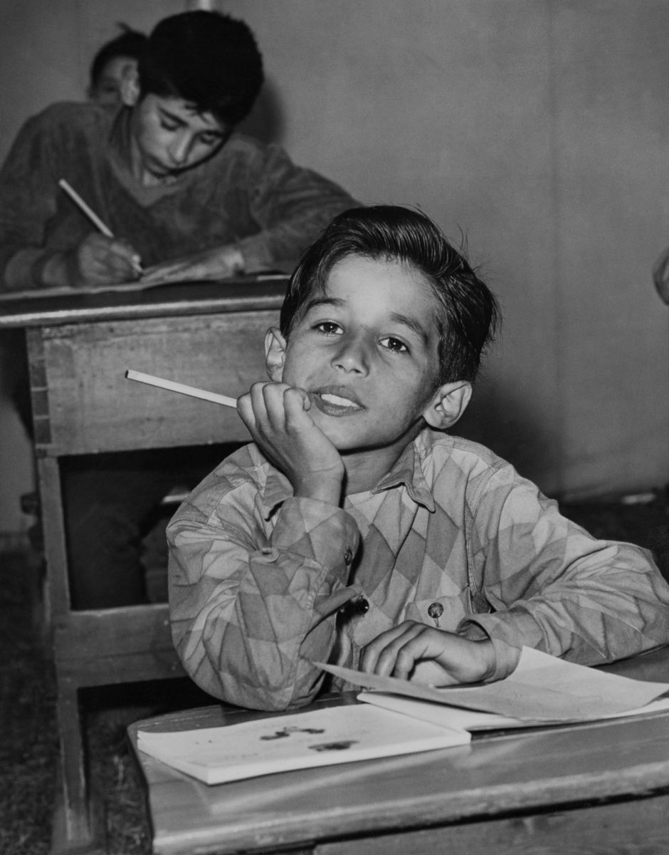 """En pojke sitter i sin skolbänk med hakan stödd i handen. Bakom honom skriver en annan pojke flitigt i sin bänk. Trots att Sverige haft skolplikt sedan 1842 har inte alla barn haft rätt att gå i skolan. Redan 1933 skrev Johan Dimitri Taikon till skolöverstyrelsen och bad om skolundervisning för romska barn. Först tio år senare blev han hörsammad, då han tillsammans med den frikyrkligt engagerade Otto Sundberg blev beviljad 1500 kronor för att starta en """"försöksskola"""". Denna verksamhet kom senare att drivas för Stiftelsen Svensk Zigenarmission, som grundades 1945 och drev sommarskola för romska elever under hela 1940- och 1950-talen.  Eleverna var mellan 6 och 60 år och satsningen blev mycket medialt uppmärksammad. Först efter att alla romer fick bli bofasta år 1959 fick samtliga romska barn möjlighet att gå i skola året om. Denna bild är tagen i sommarskolan i Örby 1957. Ett läger ska ha funnits i Örby vid Stockolmsutredningens första inventering i december 1955. Den exakta platsen för detta läger är inte känd."""