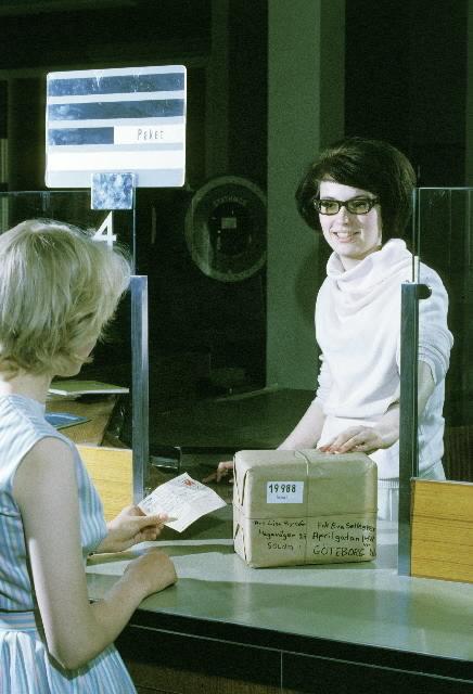 Seriebild M 32. Arrangerad situation vid paketkassan på postkontoret i Jakobsberg.  Eva, 15 år, får Lisas paket. Det kvitterade adresskortet lämnas till postkassören.