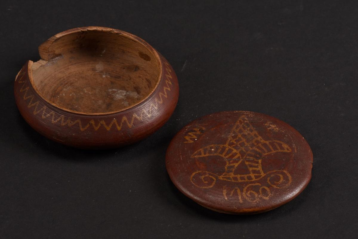 Rund, svarvad, ask med lock tillverkad av bok. Asken är målad på utsidan i rött med gula mönster; runt asken ett sicksackmönster och på locket ett årtal, 1760, samt en stiliserad lilja. Asken är skadad och en bit saknas.