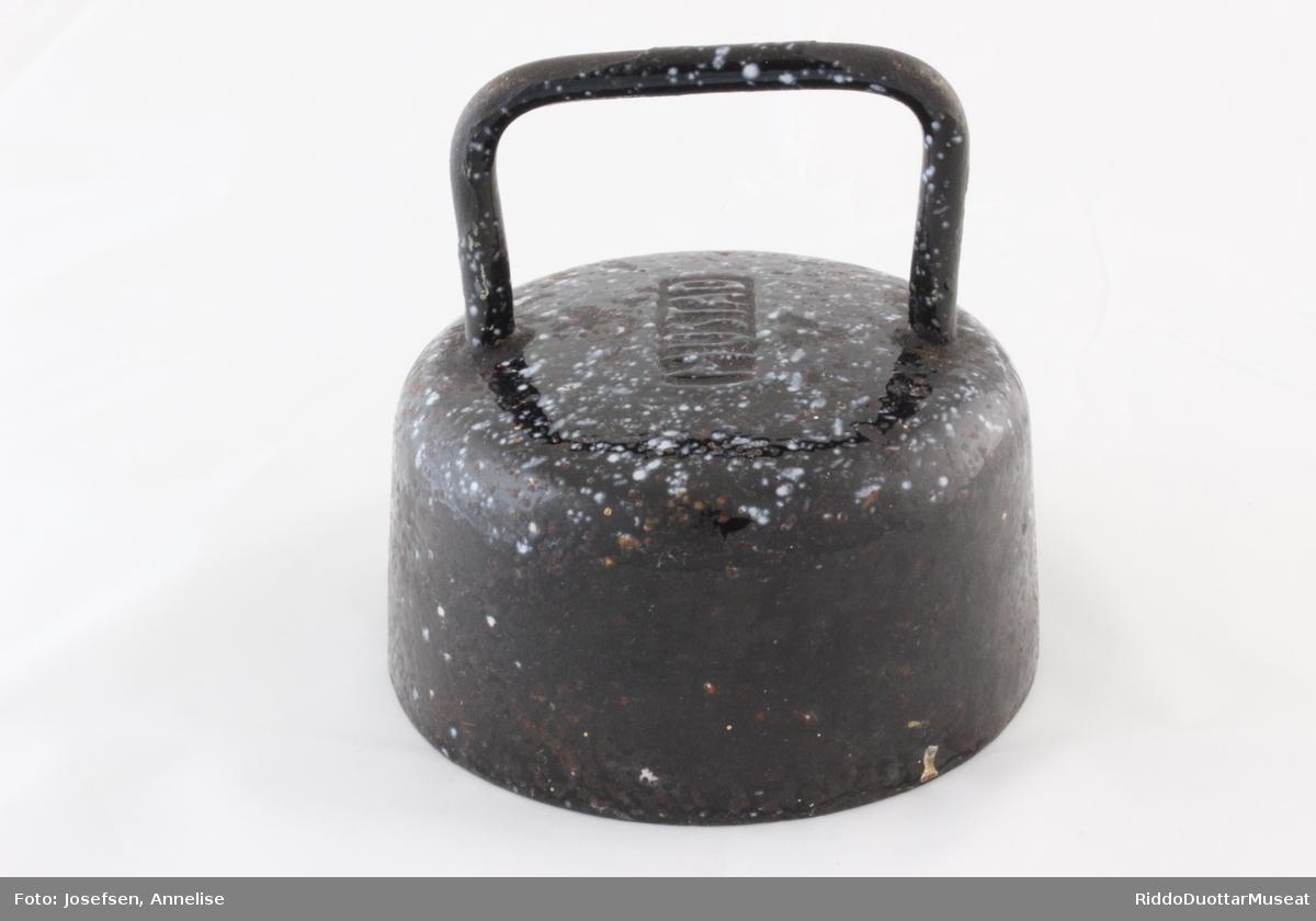 Jernlodd brukt for å trykke ned / tette lokket på kokekar. På undersiden er det spart ut et hulrom med plass til hanken eller knotten på kjelelokket. Loddet er av emaljert jern. Noen steder er emaljen slitt av slik at jernet har fått rustflekker. Undersiden er ikke emaljert.