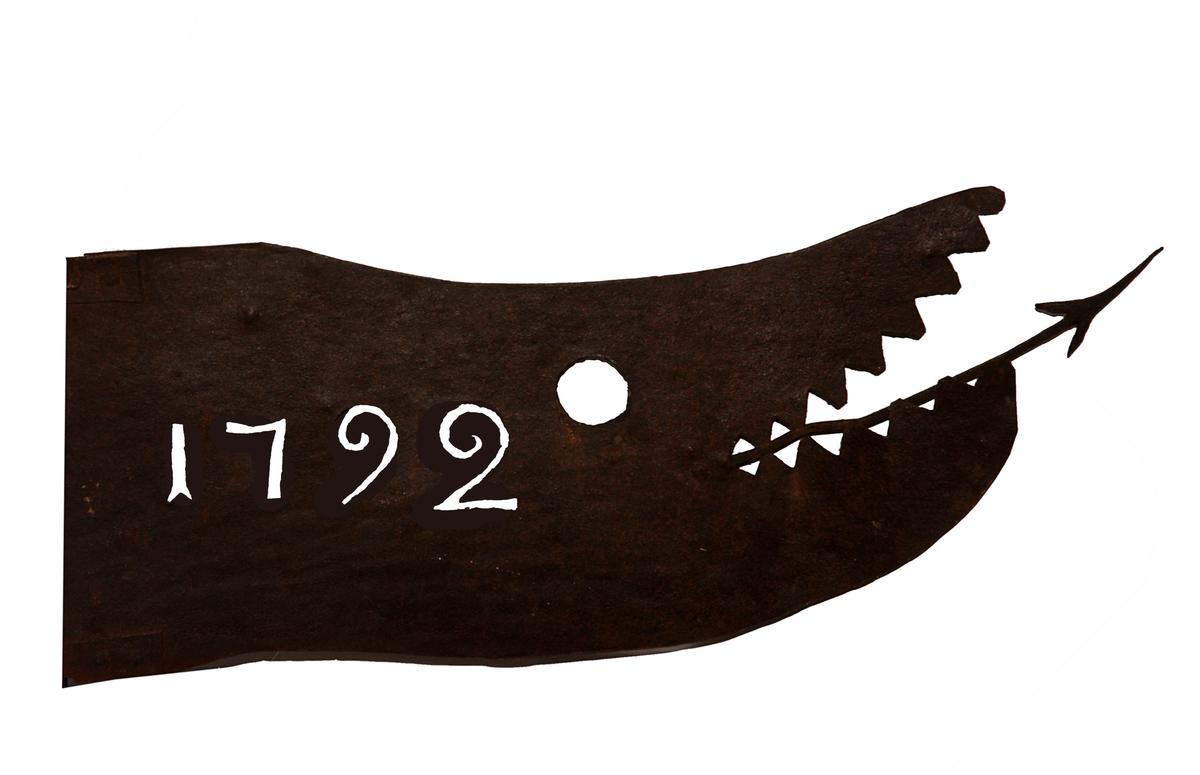""":1 Stång tillplattad med tre hål i ena änden, i andra spetsig med ring. Mått: L 2100 mm.  :2 Utsmidd i järnplåt, i form av ett drakhuvud med öppna käftar och pilformad tunga, vidhängande etikett: """"Flöjel från Hübleins kvarn i Karlstad"""". Mått: L 65 mm, H 280 mm."""