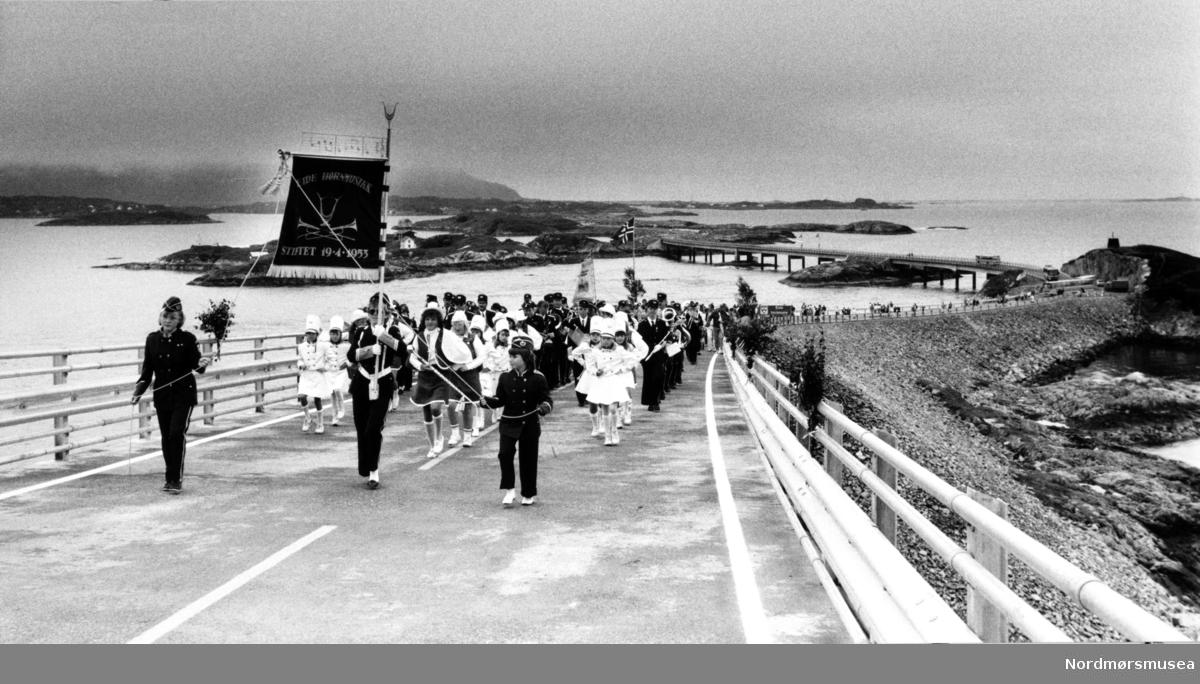 """Fra åpningen av Atlanterhavsveien mellom Averøy og Eide i Møre og Romsdal, 7. juli 1989. Atlanterhavsveien er en veistrekning på 8.274 meter. Anlegget består av åtte broer på til sammen 891 meter og går over holmer og skjær. Veien kostet 122 millioner i 1989 og var delvis bompengefinansiert. Anlegget ble åpnet 7. juli 1989 og bommen ble fjernet i juni 1999. Atlanterhavsveien er landets åttende best besøkte naturbaserte turistattraksjon (2004) med 283.500 besøkende. Veistrekningen er foreslått vernet i """"Nasjonal verneplan for veger, bruer og vegrelaterte kulturminner."""" (Kilde: Wikipedia Norge)."""