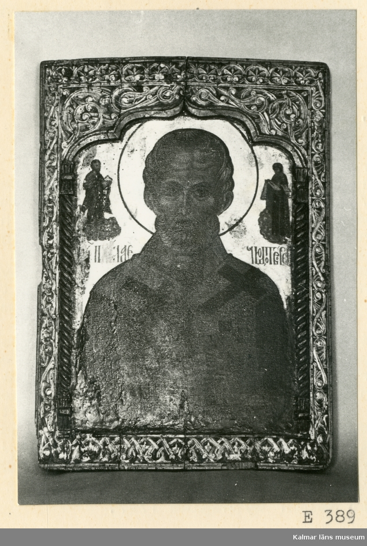 KLM 39158 Ikon. Trä. En Nikolaustavla, föreställande den helige Nikolaus av Myra. Från 1500-talet eller början av 1600-talet. På ömse sidor om Nikolaus huvud ses två människogestalter, den högra tolkas som Guds moder, den andra föreställer Kristus. Nikolaus är klädd i brungul dräkt med svarta kors, den av honom burna evangelieboken är röd till färgen. Bakgrunden är förgylld, en svart cirkel omger huvudet. Märkligast är omramningen. Två vridna kolonner med ett slags dubbelkapitäl uppbära en bruten båge. Denna från arkitekturen (ursprungligen väl den persiska) hämtade omramningen torde ej ha uppkommit tidigare än på 1400-talet, men säkerligen mest varit i bruk under följande århundrade, däremot har akantusornamenten en ännu äldre karaktär.
