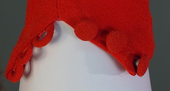 Mörkrosa creppat konstsilke, avskuren i midjan, skärp. V-ringad hals, draperat framstycke. Lång snäv ärm. Tre små inprovningar i båda ärmveck. Litet sprund i nederkant med tre klädda knappar och tygöglor. Kjolen rynkad fram, sydda inprovningar bak. Blixtlås i vänster sida. Axelvaddar. Mått i cm: rygglängd 42, kjollängd 62.