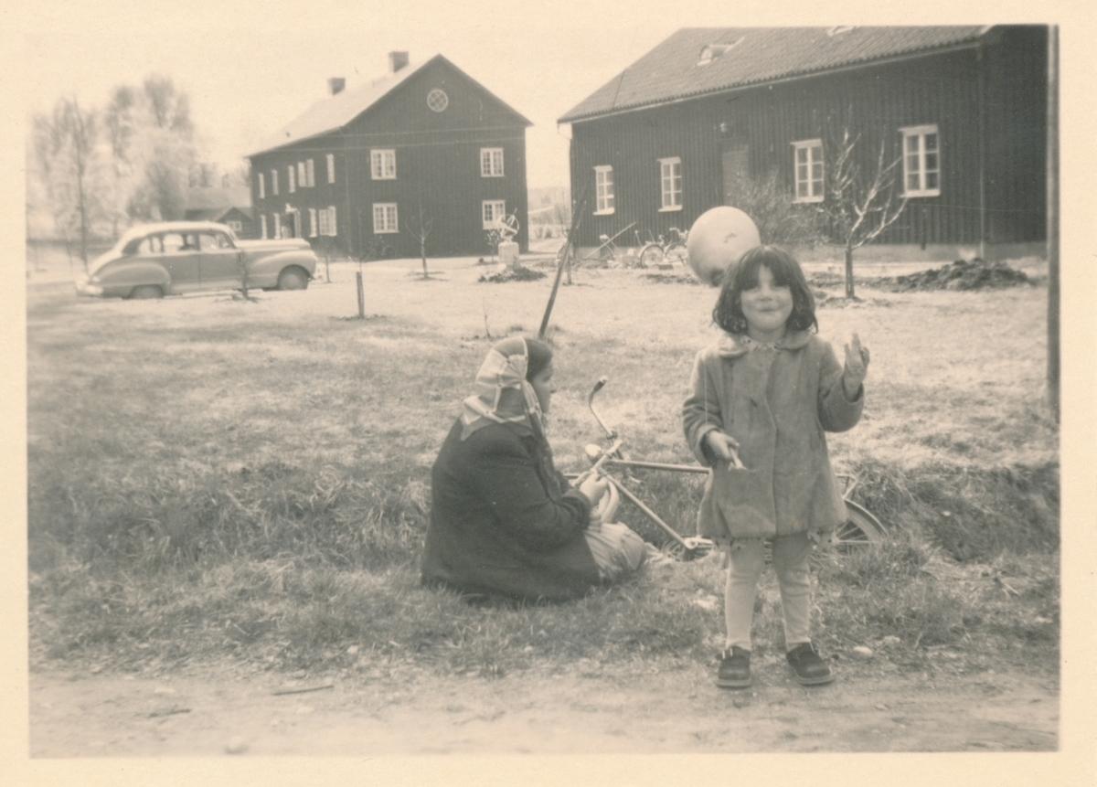 En kvinna och ett litet barn har slagit sig ned vid en vägkant. BIlden är tagen i samband med vårmarknaden i Torsby 1949.