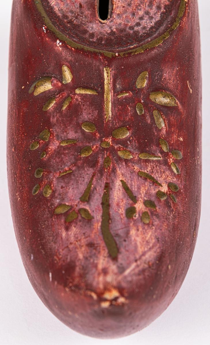 En sparbössa i keramik som föreställer en röd träsko med klack, öppning för mynt och dekorerad med blommönster upptill i guldfärg. Innuti ligger en liten knapp.