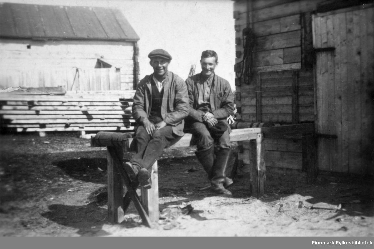 To menn sitter på bordet eller benken i Salttjern. I bakgrunnen ser vi mange planker stablet oppå hverandre.
