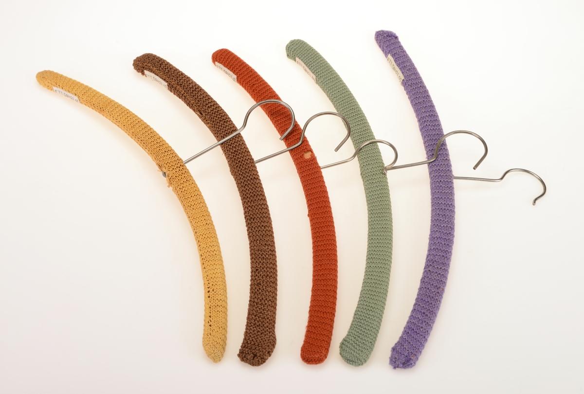 Fem enkle klesehengere laget av tre med strikket trekk. Trekkene er strikket i rettstrikk/rillestrikk. Det er strikket en remse som er sydd sammen på undersiden/langsiden av kleshengerne. Det er strikket i 5 ulike farger. For oppheng er det en enkel krok i metall.