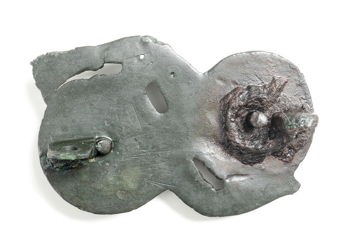 """Dräktfibula i form av ett ormöglespänne av Cu-legering. Ormfigur som slingrar likt en åtta. I de två öglorna, samt i det nedsänkta """"ögat"""" har det antagligen suttit stenar. På baksidan finns rester av fästanordningen."""