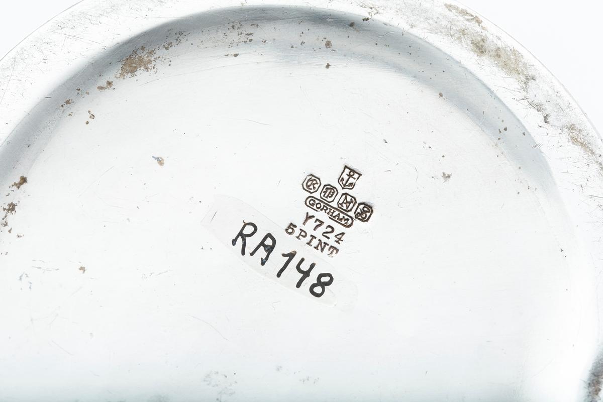 Mugge, blankt metall, bred tut, slank hank. Smal bord rundt muggen med høyt relieff, derunder siselerte blomsterrosetter, bånd og medaljonger. Stempel:? Under bunden er innrisset JVB.