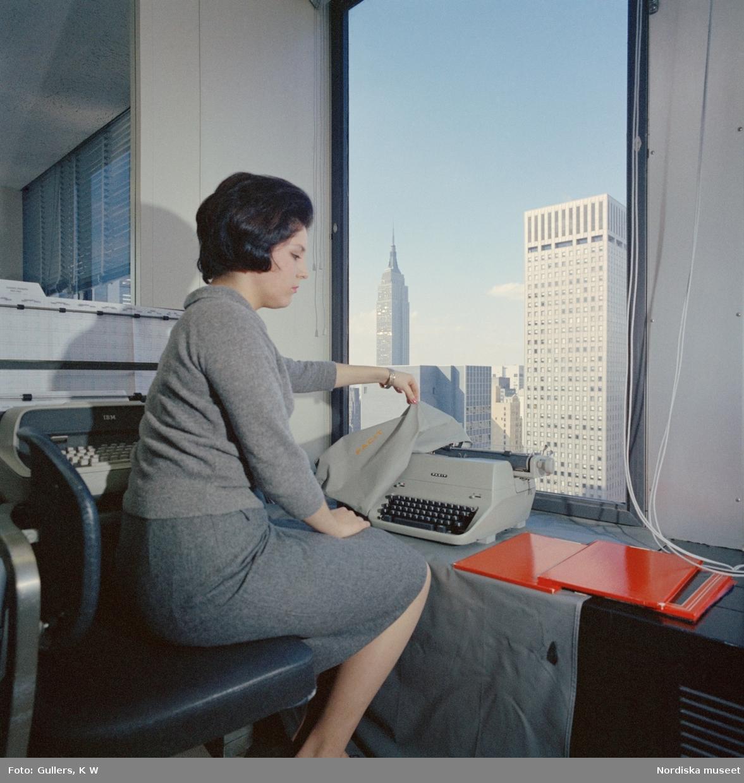 Facit-New York, 1960-tal. En kvinnlig modell avtäcker en Facit skrivmaskin sittande  invid ett fönster med utsikt över Empire state building.