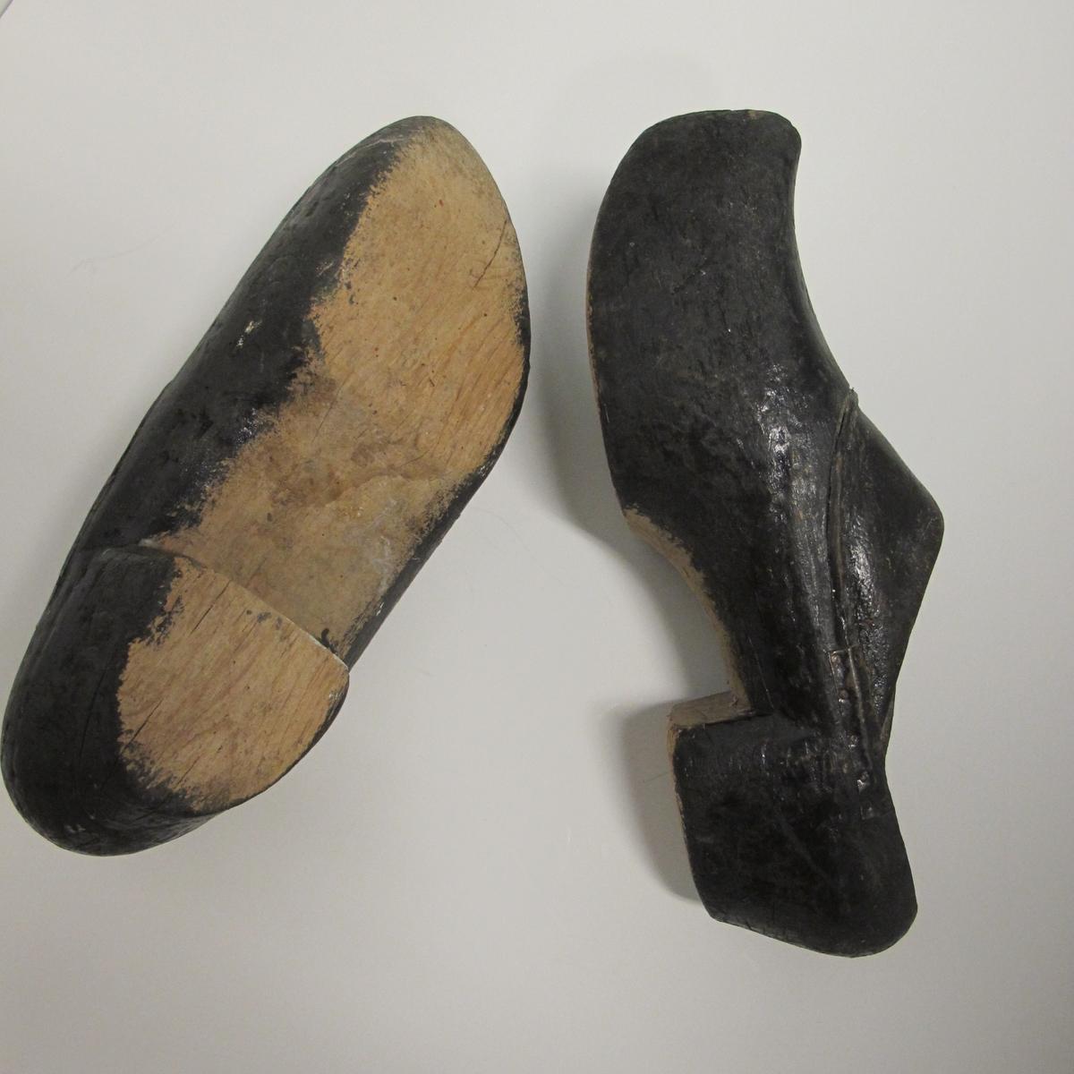 Skoene er sorte, med tre i bunn og i deler av kappen, der tuppen gå opp i en spiss foran. Den har noen innrissninger som ikke er tydet. Bare stykket nærmest vristen er av lær.