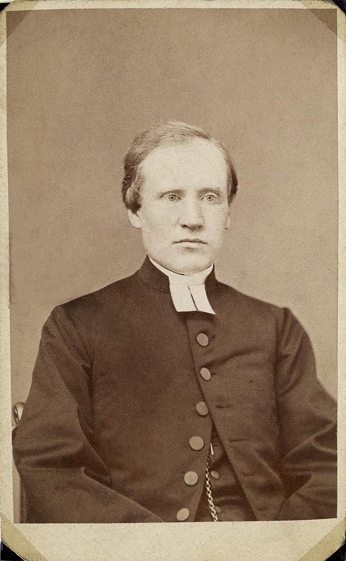 Foto av en man i prästrock och prästkrage. På västen skymtar en klockkedja. Midjebild, halvprofil. Ateljéfoto.