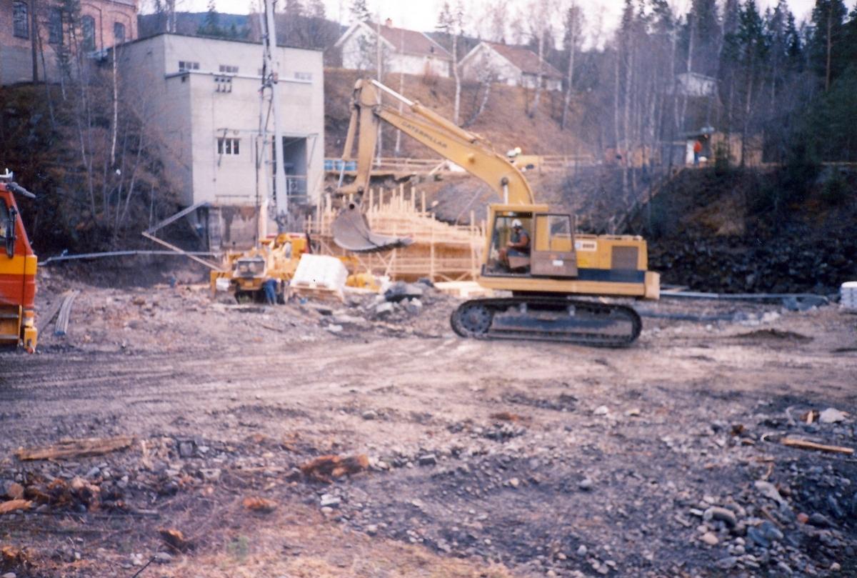 Anleggsarbeid med gravemaskin nedenfor Kistefoss II og det eldste tresliperiet. Bygging av forskalling for å kunne støpe forstøttningsmur. I bakgrunnen er to hvite bolighus og en garasje synlige. Vannføringen i Randselva er stanset og tørrlagt for arbeidet.