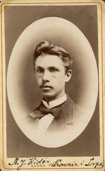 Foto av en ung man i kavajkostym, stärkkrage och fluga.  Brö