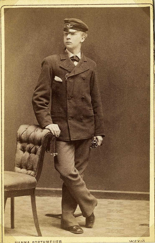 Foto av en ung man i kavajkostym med fluga och skolmössa. Vid kavajslaget skymtar en pincené med snodd.  Han lutar ena handen mot ryggstödet på en stoppad stol.  Helfigur, halvprofil. Ateljéfoto.