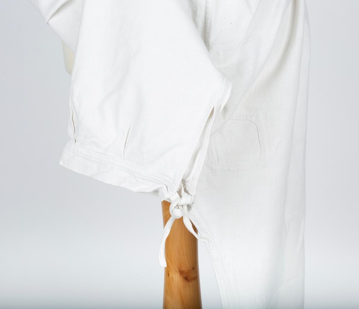 Knelange underbenklær. Lang splitt i begge sider. Søm, dobbeltsøm,i sidene, midt forran og midt bak. Spisse kiler i skrittet. Fasongkiler øverst mot bakstykets linning. Bakstykkets linning har bendelbånd og et sekundært bånd av mønstret stoff som kan knyttes forran.  Forstykkets forlengede linning knappes midt bak, lerretsknapp. Små legg ved linningene Lapp på høyre bakstykke.  Bukseben har splitt , linning og knyttebånd.  Gitt av Åse Huseby, Oppegård, Frogn. Formidler Greta Christiansen. Brukt av søstrene Christiansen, på Brevik