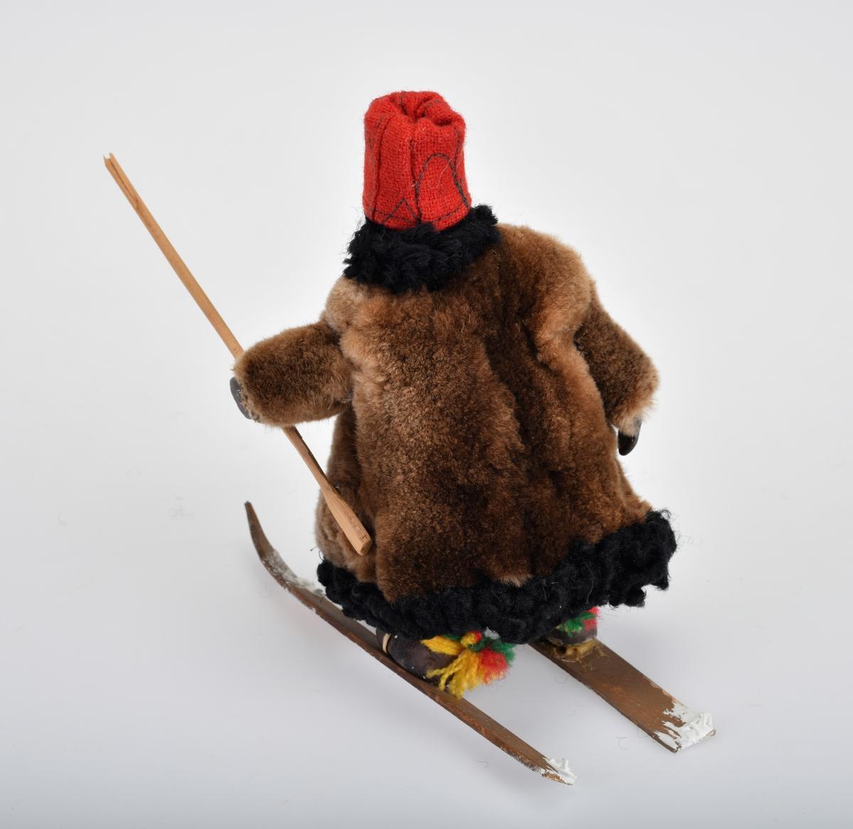 Liten damefigur i pelskåpe med ski på beina, hun har en langstav i hånden.