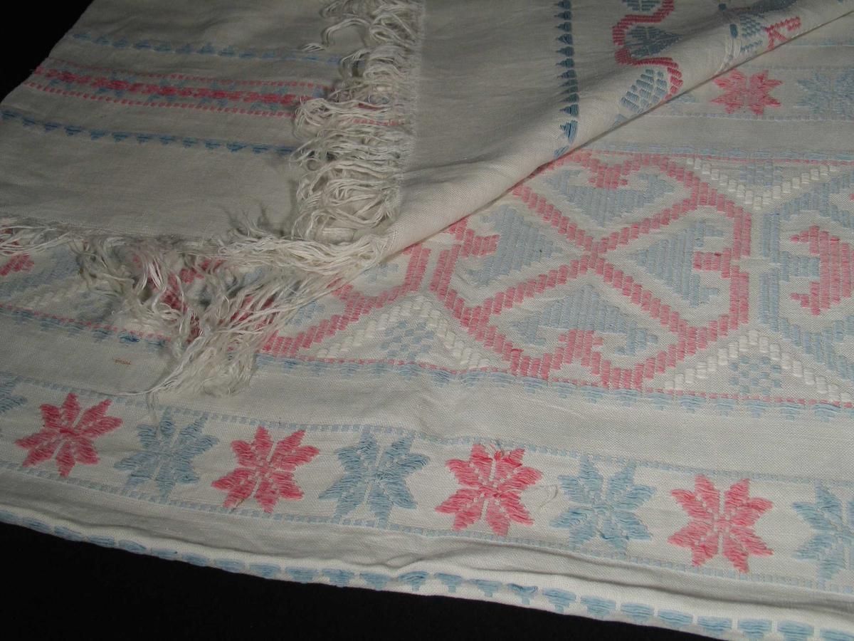 Hvit linløper med broderi i rødt, hvitt og blått. Den har frynser i endene. Motivet er en bryllupsscene med spillemenn og draktkledde kvinner og menn. Løperen har ulike border; hjerteformet, åttebladsrose osv.