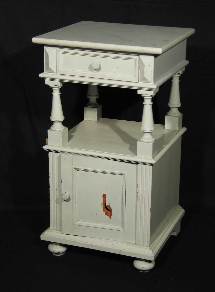 Hvitmalt nattbord i tre med marmorplate. Det har øverst en skuff og fire profilerte søyler skiller denne fra underskapet.