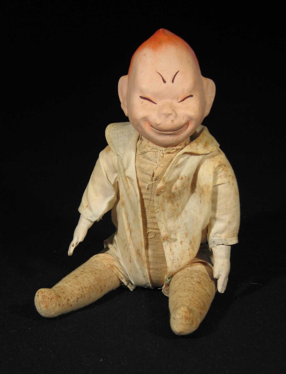 Dokkemann med asiatisk utseende. Han har porselenshode, hender og stoppet tøykropp. Han er iført tynn hvit drakt med krage. Den er kneppet foran med tre knapper.