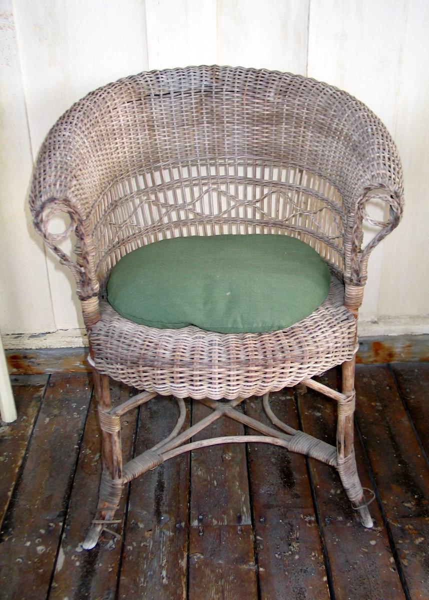 Kurvstol med rundt sete og utoverbrettet rygg. Stolen har gjennombrutt mønster i ryggen og flettet dekor langs armlener.