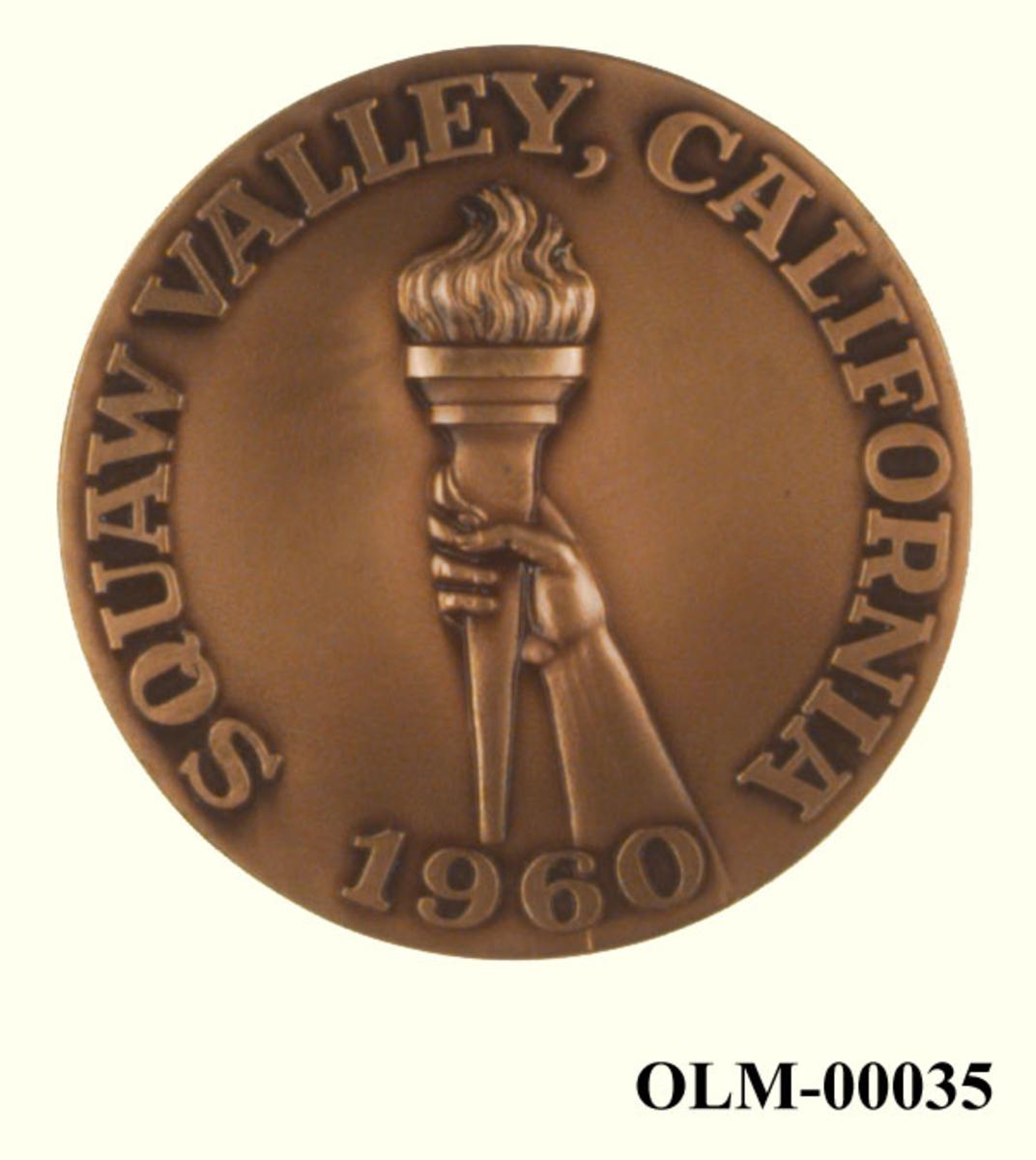 Bronsefarget medalje. På den ene siden finner man emblemet til de olympiske vinterleker i Squaw Valley i 1960. På den andre siden er det motiv av en hånd som holder en olympisk fakkel.