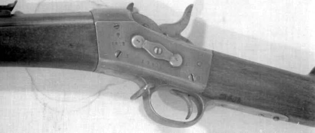 Sivil norsk enkeltskudds rifle med Remtington- rolling-block system med randtenning ombygget fra et militært gevær. Rund riflet pipe Jern justerbart baksikte.Forsikte mangler. Todelt trekolbe med messing kolbekappe. Pipen er festet til kolben med to jernbånd Pussestokk i jern med messing tupp. To remfester