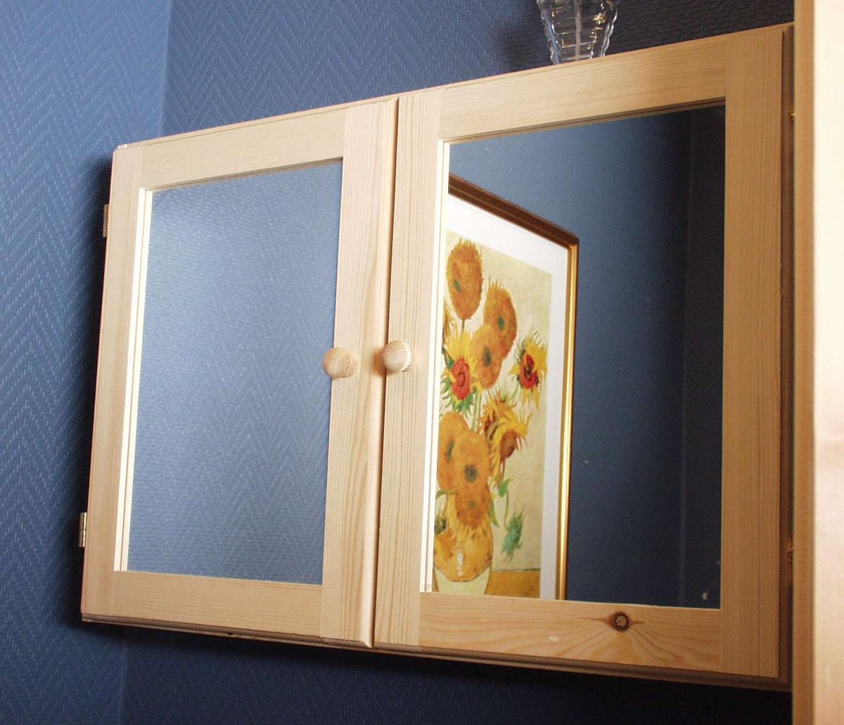 Skap i ubehandlet furu med speil i dørene. Det er ei hylle inni og ryggen er laget av finérplate.