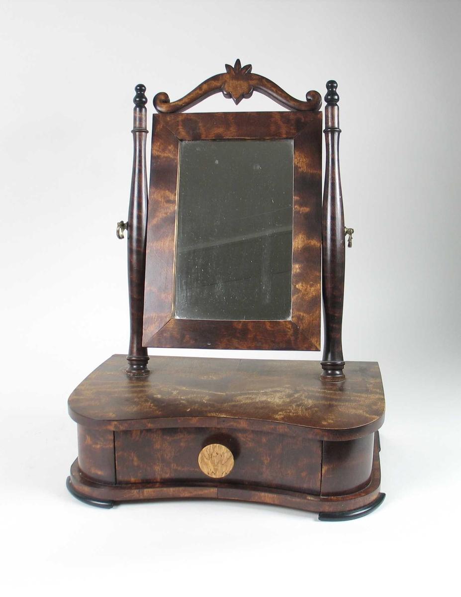 Bordspeilet er av furu med beiset bjørkefiner. Speilet har en skuff med sekundær knott av ubehandlet valbjørk. Speilrammen, søylene og dekoren på toppen av speilet er ikkje finert. Speilet er festet til søylene med en messingskrue med dekorativ hempe på hver side.