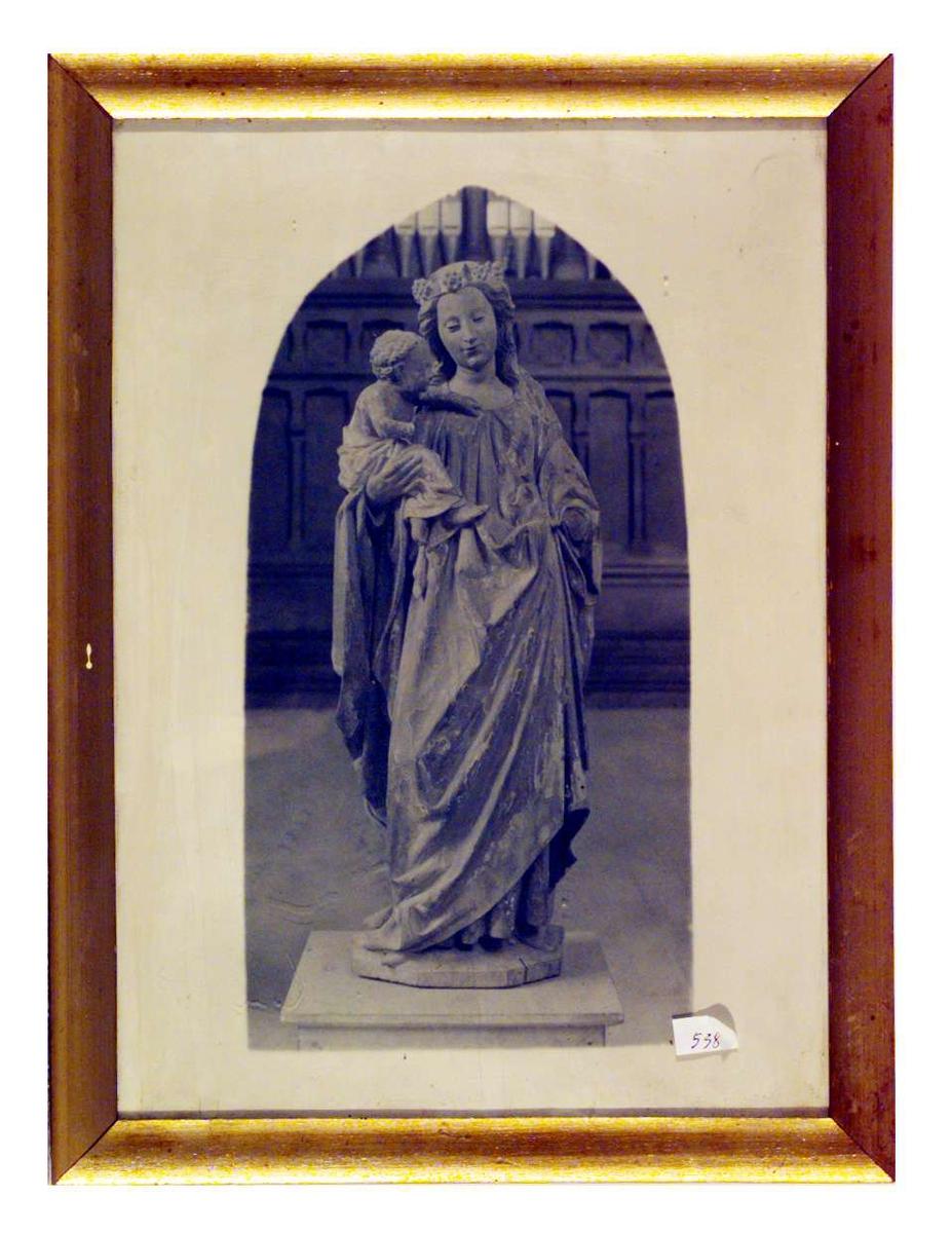 Bildet er en sort/hvit gjengivelse av en malt treskulptur. Skulpturen fremstiller en stående Madonna med Jesusbarnet på armen.