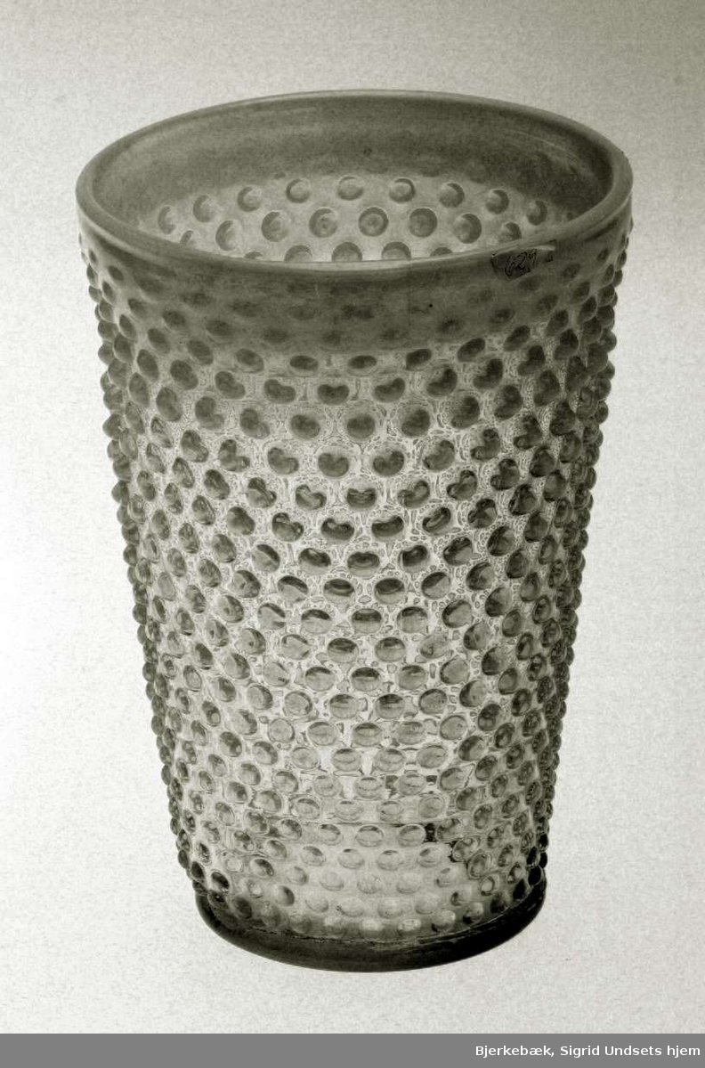 Blomstervase med konisk form. Den er i glass og yttersiden er 'knoppete'. Kanten av vasen og 'knoppene' har en melkehvit farge. Vasen er sprukket.