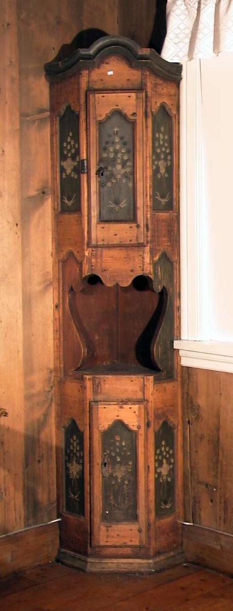 Høyt hjørneskap med to skap med åpent rom i mellom. Skapdørene og sidene har speil med hvit dekor på grønn bunn. Skapet er veggfast.  Nederste skapdør er løs i hengslet. Nøkkel mangler i nederste dør.