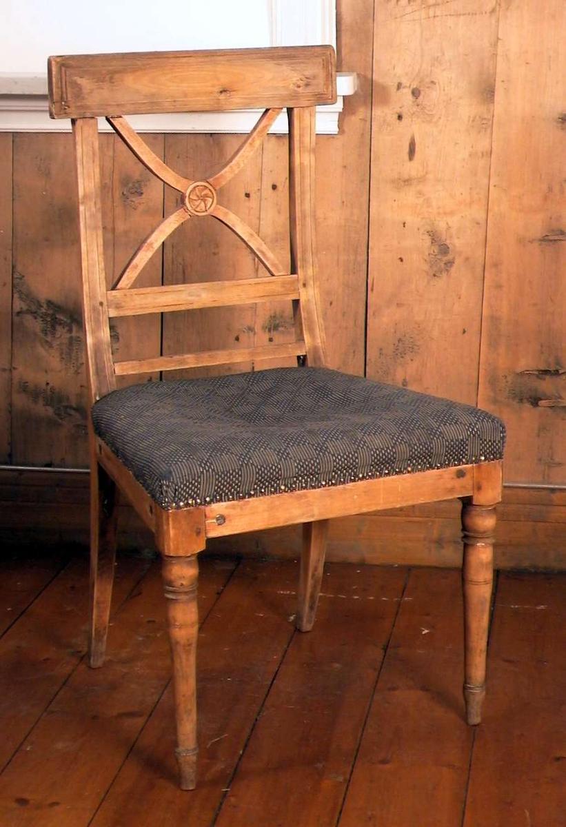 Trehvit spisestuestol med Andreaskors i ryggen og med stoppet sete. Stoffet i setet er blått og beige i et rutemønster. Setet er helt nedsittet.