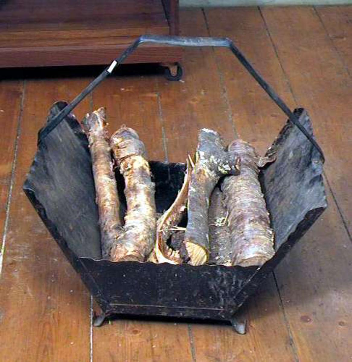 Vedkurv på fire føtter med utskrånende sider og hank. Den er av sort metall (jern).