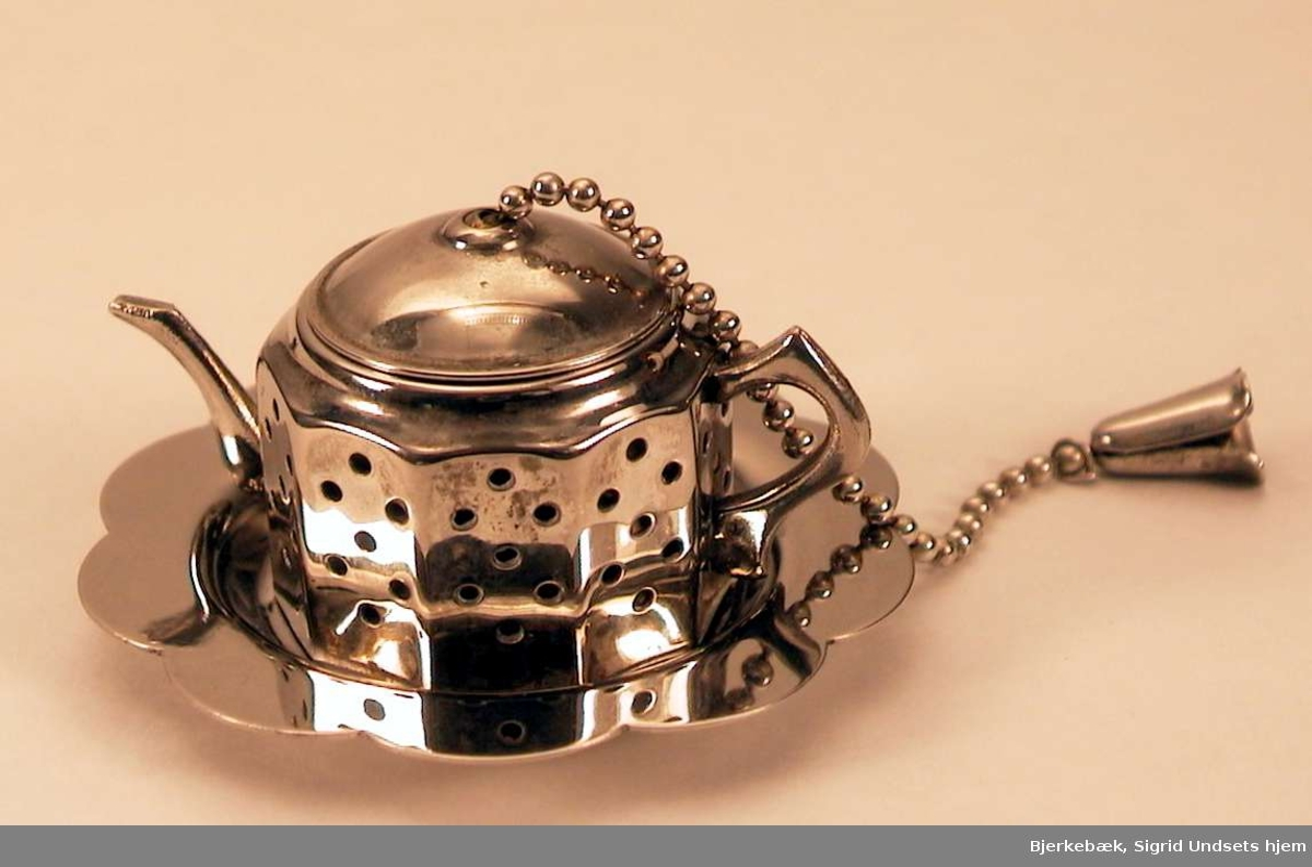 Tedypper med skål i et sølvlignende metall. Tesilen er  formet som en tekanne med hank og tut og med en lenke i lokket.